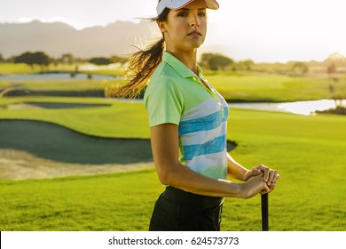 Portrait of young female golfer with golf club standing on field. Beautiful young woman on golf course on summer day.