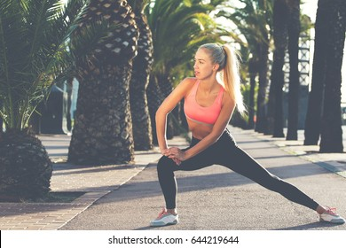 Portrait of a young female jogger stretches legs muscles before a fitness training on the fresh air outside, charming sports woman with beautiful slim figure working out outdoors in sunny summer day