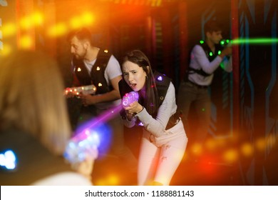 Portrait of young female laser tag player with laser pistol in room with bright beams