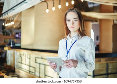 Portrait of young female manager looking at camera with tablet computer in her hands and badge around her neck
