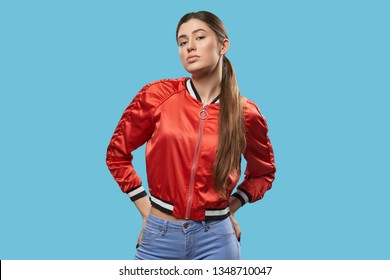 Portrait of young female model on blue background. Pretty girl with beautiful make up, long hair, ponytail, wearing in bright red bomber posing and looking at camera. Youth style.