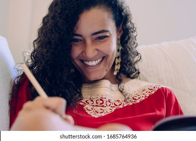 Portrait of young female with muslim lifestyle. Beautiful ethnic woman writing on a notebook at home. Moroccan female with traditional clothes with copyspace. African culture indoors at the house.