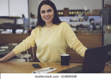 Portrait of young female owner of famous restaurant working on organizational issues using modern technology and wireless 4G internet. Successful businesswoman looking on camera with smile on face