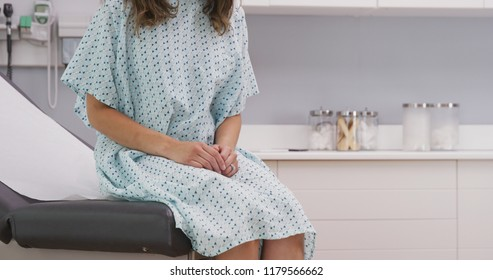 Portrait of young female patient seated on clinic chair wearing hospital gown