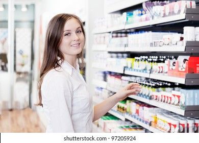 Portrait of young female pharmacist standing in pharmacy store