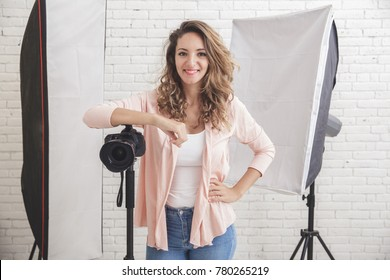 portrait of Young female photographer with camera in professionally equipped studio