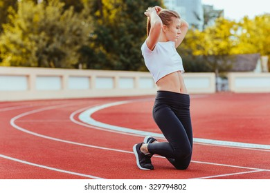 Portrait of a young female runner straightens her hair on outdoor stadium