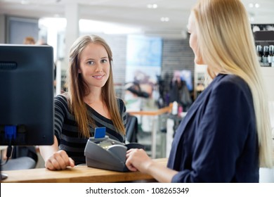 Portrait of young female sales clerk standing by counter with customer at parlor