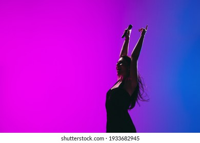 Portrait of young female singer isolated on blue-pink background.