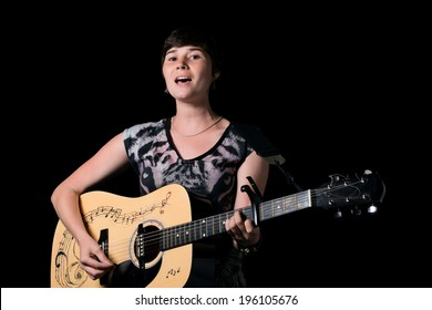 portrait of young female singer with a wooden guitar on black background