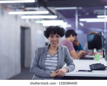 portrait of young female software developer at busy startup office with her multiethnic business team in background