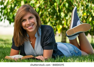 Portrait of a young female student with book at the campus