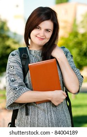 Portrait of a young female student with books at the campus
