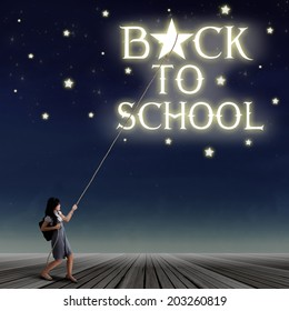 Portrait of young female student pulling down a back to school text and the stars with rope