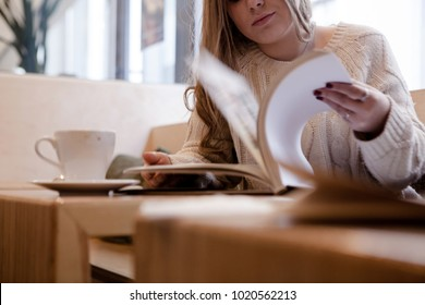 Portrait of young female student sitting in modern coffe shop and studing