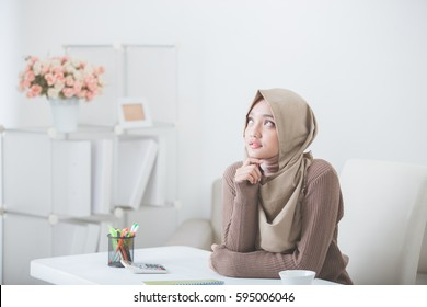 portrait of young female student thinking and looking up to copyspace