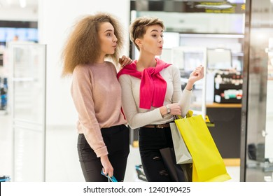 Portrait of young female students go shopping at the big city mall, holding coloured shopping bags, keep their eyes open not to miss shopping opportunities . Sale, Consumerism and People Concept.