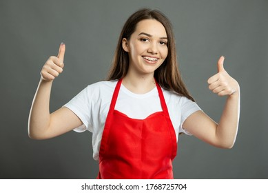 Portrait of young female supermarket employee showing double thumb up gesture on gray background