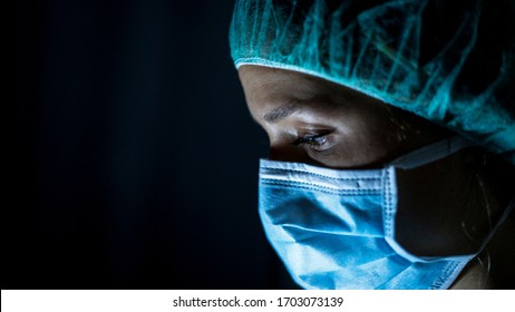 Portrait of young female surgeon, wearing mask and a surgical mask, in front of black background