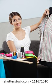 Portrait of young female taking measurement of a shirt with dressmaking accessories on table