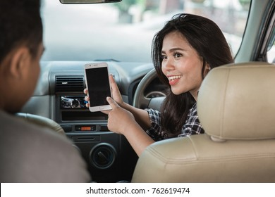 portrait of young female taxi driver looking for direction via GPS on her mobile phone