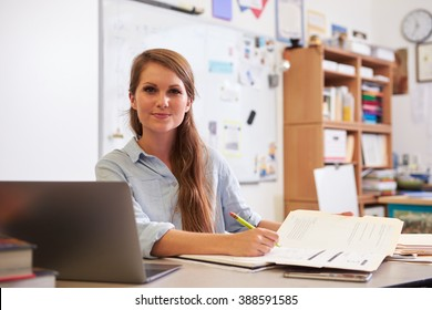 Portrait of young female teacher at desk looking to camera