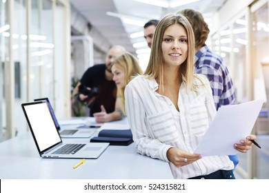 Portrait of young female team leader of talented journalists organizing work of members motivates and inspire them to make researching, standing on blurred background in modern coworking space