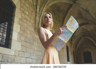 Portrait of young female tourist checking out the sights while reading a map, gorgeous woman holding a map while touring abroad,stylish hipster studying a map while standing in antique town in summer