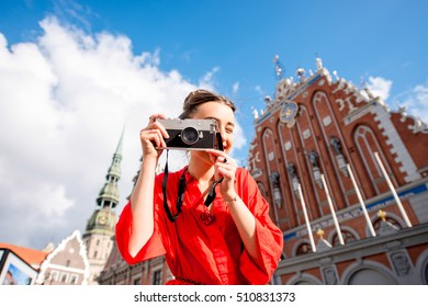 Portrait of a young female tourist with photo camera on the main old town square in Riga. Woman having great vacations in Latvia