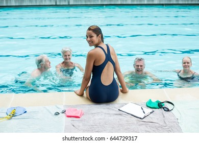 Portrait of young female trainer assisting senior swimmers at poolside