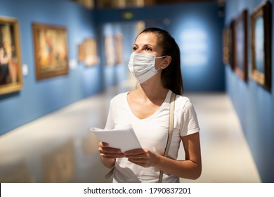Portrait of young female visitor in protective face mask with paper guide at paintings exposition, local tourism during pandemic situation