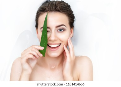 Portrait of young female woman adult with clean pure skin taking spa smiling relaxing in bath with aloe white soap shampoo water. Skin beauty health care concept. Body part bare shoulder