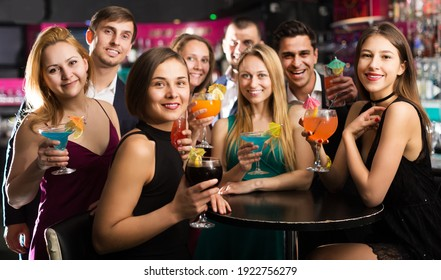 Portrait of young females and males celebrating corporate in the bar at night