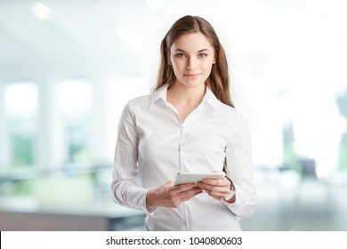 Portrait of young financial assistant businesswoman using digitla tablet while standing at the office.