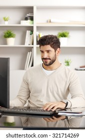 Portrait of young financial assistant sitting at office and working on his personal computer.