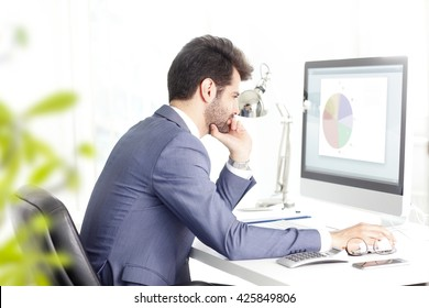 Portrait of young financial businessman sitting in front of computer and thinking to solve the problem.