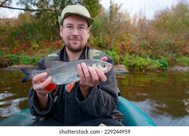 Portrait of a young fisherman with chub