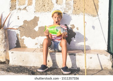 Portrait of a young fisherman sitting near the fishing pole amazed of his big fish. Thunderstruck sailor boy with wool cap and a striped t-shirt. Lifestyle happiness, positive, funny outdoor concept