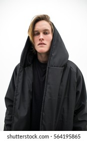 portrait of young fit blond haired man in dark coat on the white background