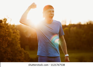 Portrait of young fit male athlete enjoying victory in the marathon outdoor. Handsome runner win the competition, rise the hand and scream, enjoy success. Sport and people concept.