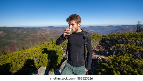 Portrait of young fit male hiker drinking tea on top of the mountain on a warm sunny day, autumn time. Beautiful overview point. Lifestyle and sport concept.