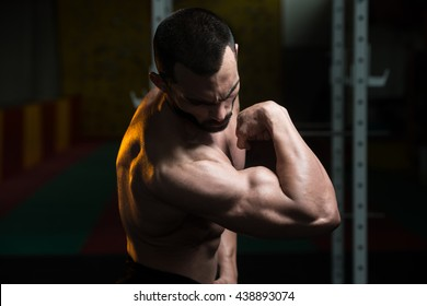 Portrait Of A Young Fit Man Flexing Front Biceps Pose - Muscular Athletic Bodybuilder Fitness Model Posing After Exercises