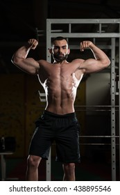 Portrait Of A Young Fit Man Showing Front Double Biceps Pose - Muscular Athletic Bodybuilder Fitness Model Posing After Exercises