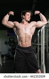 Portrait Of A Young Fit Man Showing Front Double Biceps Pose - Muscular Athletic Bodybuilder Fitness Model Posing