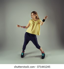 Portrait of young fitness female dancing zumba in studio. Energetic woman doing aerobics exercise. Sport, leisure activity and lifestyle.