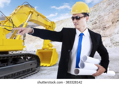 Portrait of young foreman holding blueprint and working in the construction site with excavator on the back