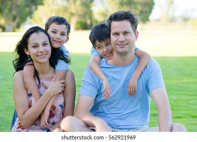Portrait young friendly happy family with sons sitting relaxed smiling in park outdoors, blurred background.