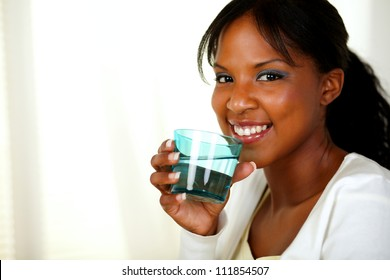 Portrait of a young friendly healthy lady smiling and drinking fresh water while looking at you. With copyspace.