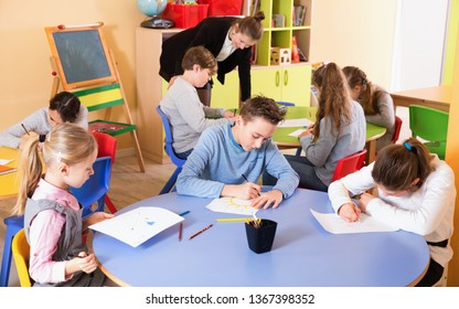Portrait of young friendly smiling teacher woman at lesson with diligent school kids
