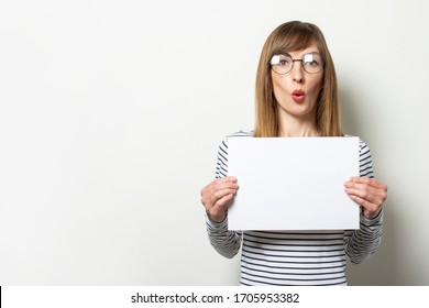 Portrait of a young friendly woman in a long-sleeve sweater and glasses with a surprised face holds a blank sheet of paper on light background. Emotional face. Gesture shock, surprise. Copy space